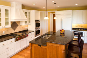 Residential kitchen showing granite counter tops, large center island, custom cabinetry, and stainless steel appliances.
